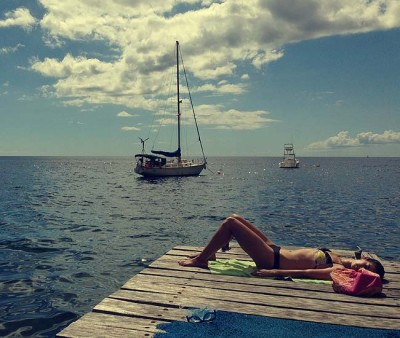 Woman sunbathing at the end of a pier with sailboats in the background on the Caribbean island of Dominica