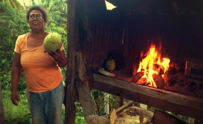 Travel with Locals as woman prepares a roasted breadfruit over an open flame on the Caribbean island of Dominica