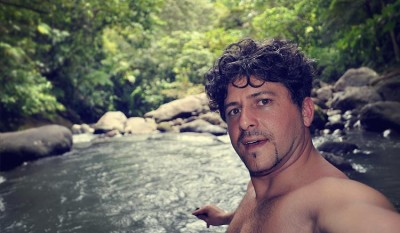 Antimo looking into the camera in middle of a river on the Caribbean island of Dominica