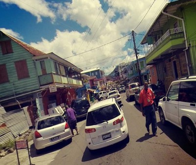 The streets of Dominica, with cars, people and colorful buildings.