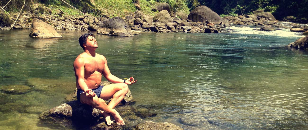 Man meditating in a river on Dominica